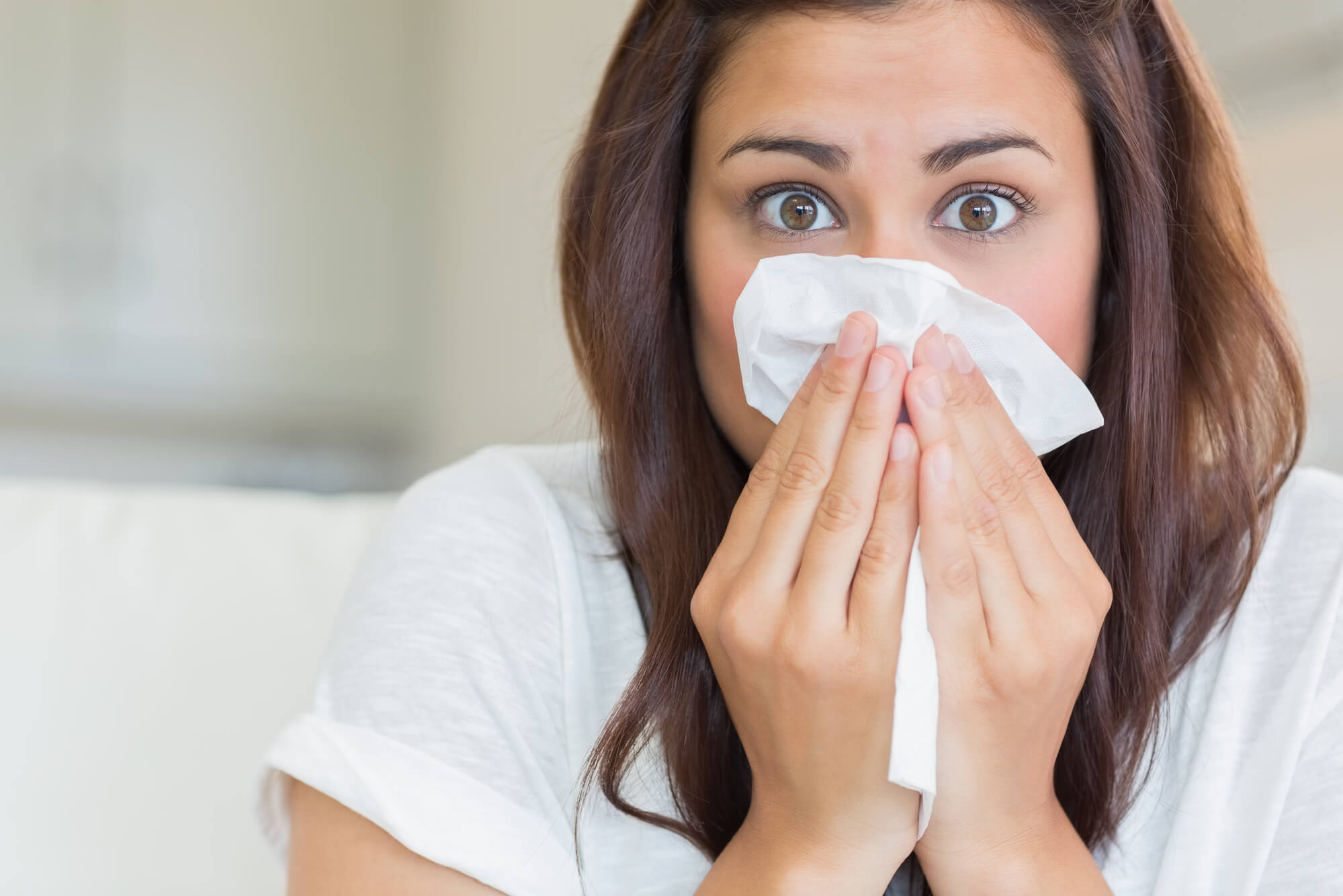 woman sneezing into tissue from allergies