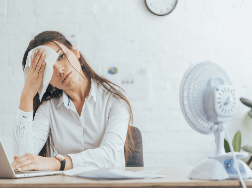 woman sweating inside office because of a broken ac system