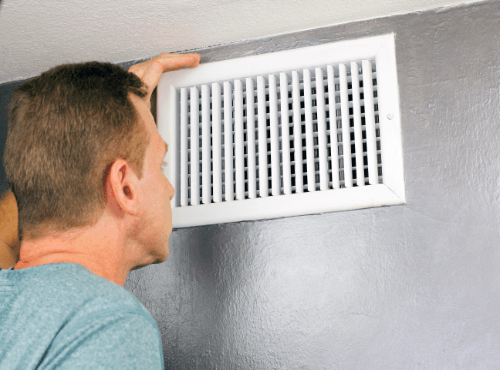 man inspecting a vent in a home